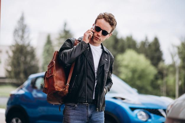 Bel homme à l'aide de téléphone par la voiture Photo gratuit