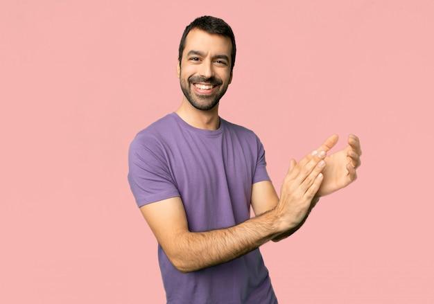 Bel homme applaudissant après présentation lors d'une conférence sur fond rose isolé Photo Premium