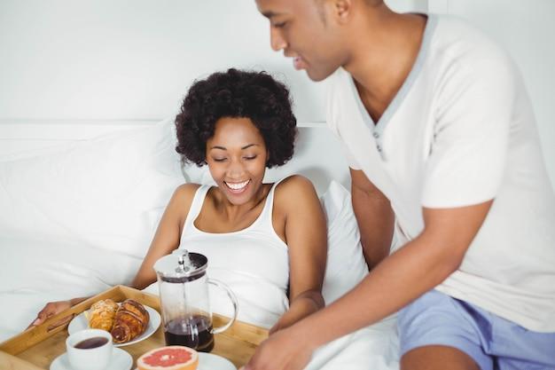 Bel homme apportant le petit déjeuner à sa petite amie sur le lit Photo Premium