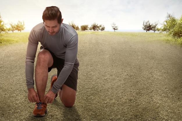 Bel homme asiatique à genoux attachant des chaussures de course se prépare pour le jogging Photo Premium