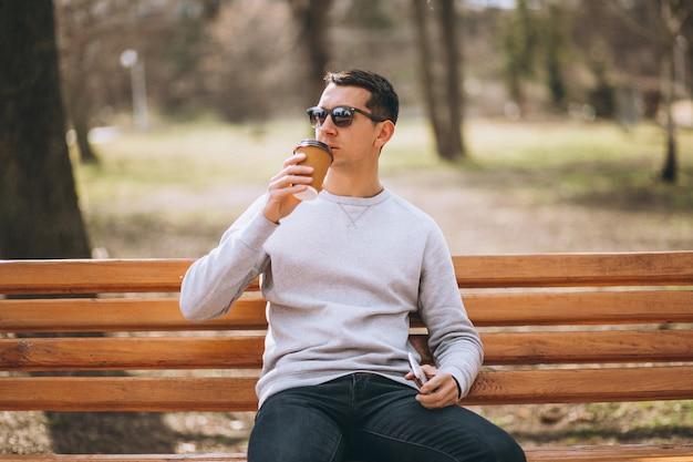 Bel homme assis dans parc boire café et utilisation téléphone Photo gratuit