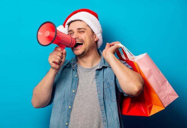 Bel homme au chapeau de noël avec fort-hailer et sacs à provisions Photo Premium