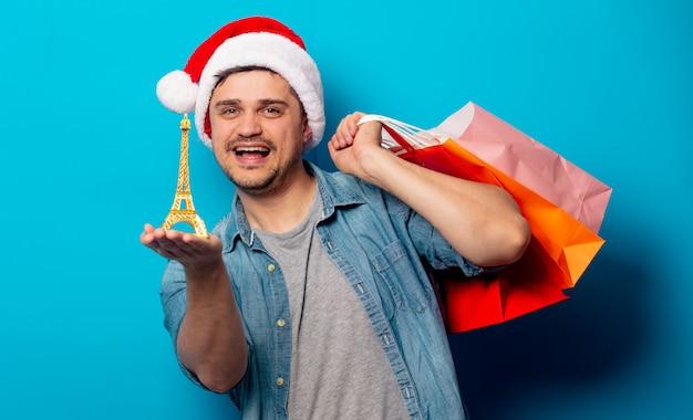 Bel homme au chapeau de noël avec des sacs à provisions et la tour eiffel Photo Premium