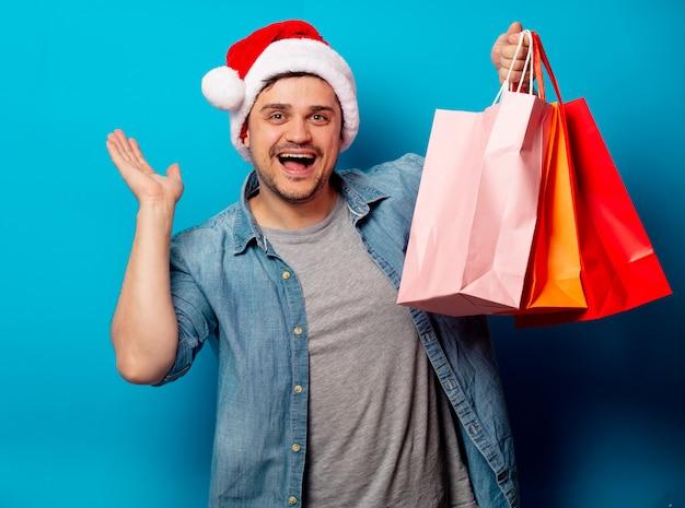 Bel homme au chapeau de noël avec des sacs Photo Premium