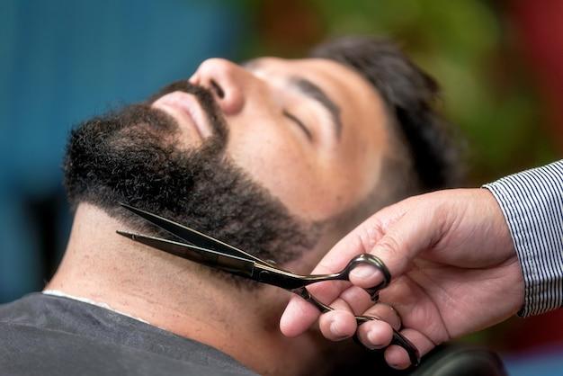 Bel homme ayant un rasage avec des ciseaux au salon de coiffure. Photo Premium