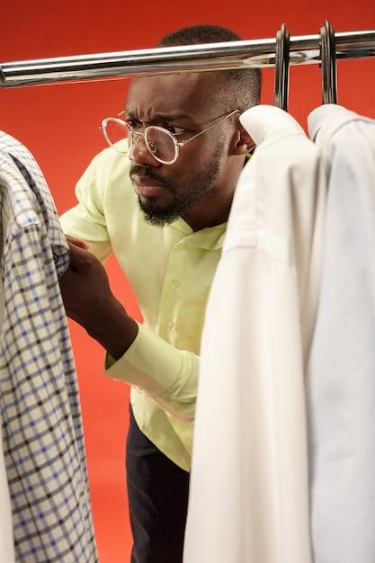 Bel Homme Avec Barbe En Choisissant Une Chemise Dans Un Magasin Photo gratuit