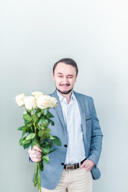 Bel homme à la barbe debout sur un fond gris avec un bouquet de roses blanches Photo Premium