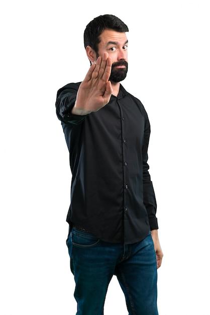 Bel homme avec barbe faisant signe d'arrêt sur fond blanc Photo Premium
