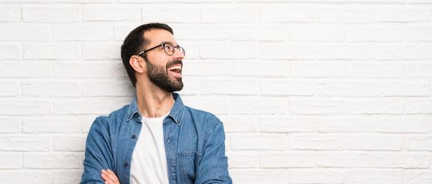 Bel homme à la barbe sur mur de briques blanches heureux et souriant Photo Premium