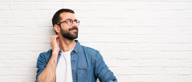 Bel Homme à La Barbe Sur Mur De Briques Blanches Pense à Une Idée Photo Premium