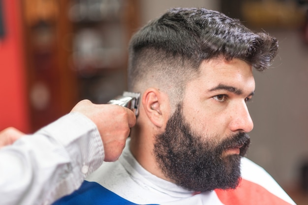 Bel homme barbu, se faisant couper les cheveux par un coiffeur Photo Premium
