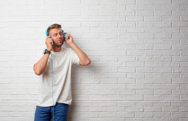 Bel homme blonde écoute de la musique avec un casque Photo Premium
