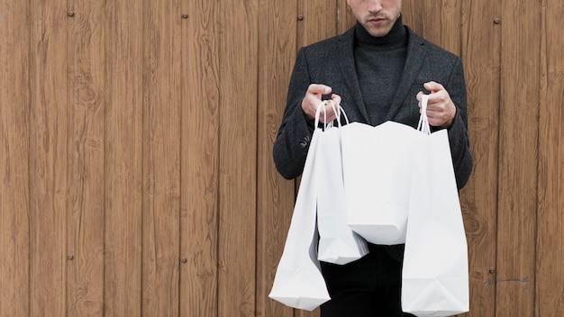 Bel homme cherche dans sacs à provisions Photo gratuit