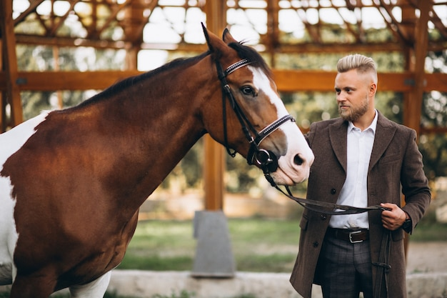 Bel homme en costume au ranch à cheval Photo gratuit