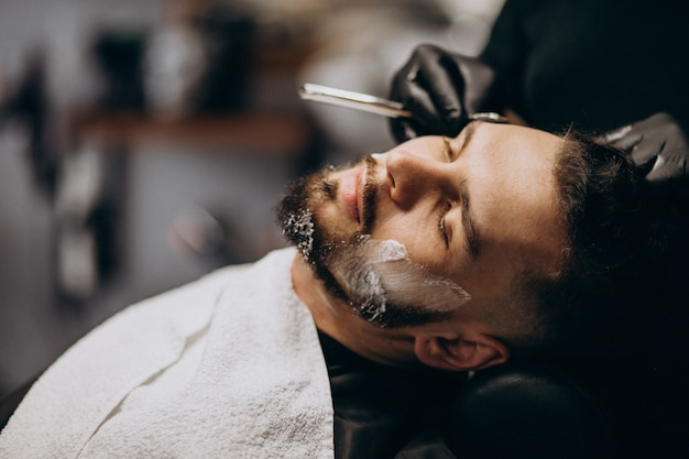 Bel Homme Coupe La Barbe Dans Un Salon De Coiffure Photo gratuit