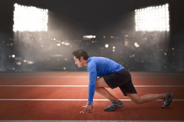 Bel homme de coureur asiatique en position prête à courir Photo Premium