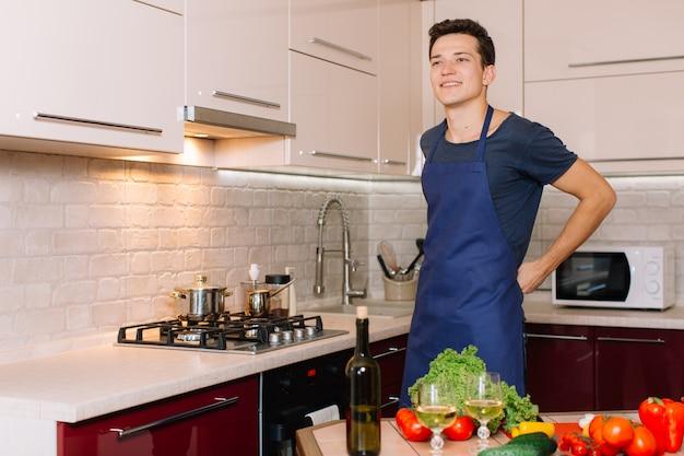 Bel homme cuisine dans la cuisine et souriant Photo Premium