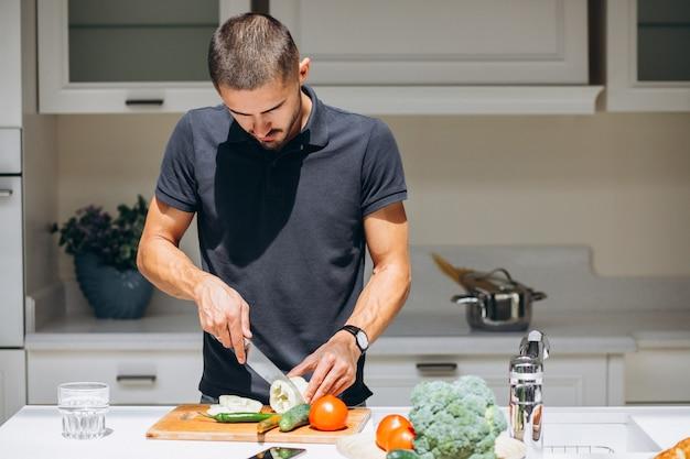 Bel homme cuisine petit déjeuner à la cuisine Photo gratuit