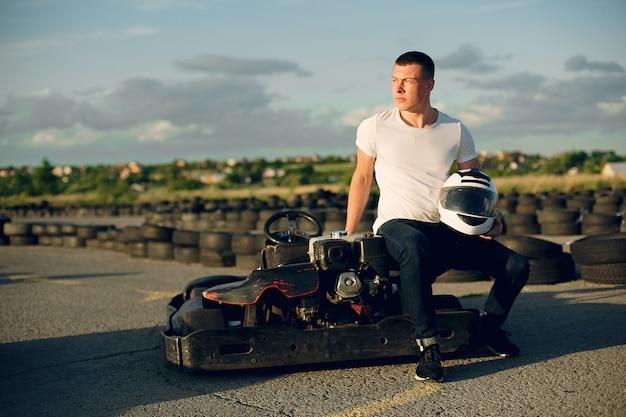 Bel homme dans un karting avec une voiture Photo gratuit