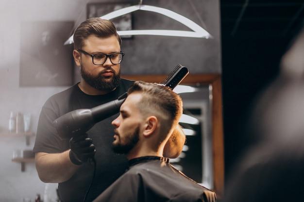 Bel Homme Dans Un Salon De Coiffure Coiffant Les Cheveux Photo gratuit