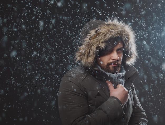 Bel homme dans la tempête de neige Photo gratuit