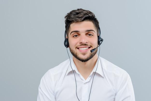Bel homme du moyen-orient travaillant avec casque répondant à des appels d'affaires en tant que répartiteur de support technique isolé sur fond gris Photo Premium