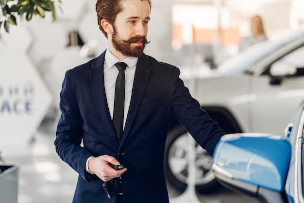 Bel homme élégant dans un salon de l'automobile Photo gratuit