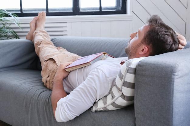 Bel Homme Endormi Sur Le Canapé Avec Un Livre Photo gratuit