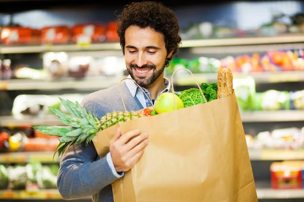 Bel homme, faire du shopping dans un supermarché Photo Premium