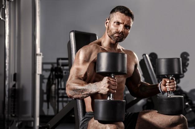 Bel homme avec de gros muscles, posant à la caméra dans la salle de gym Photo Premium