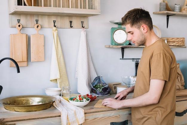 Bel homme, hacher les légumes sur une planche à découper pour faire de la salade Photo gratuit