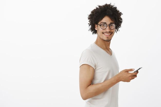 Bel Homme Hipster Dans Des Verres Tenant Le Smartphone Et Souriant Photo gratuit