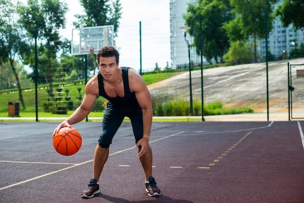 Bel homme jouant avec le ballon de basket Photo gratuit