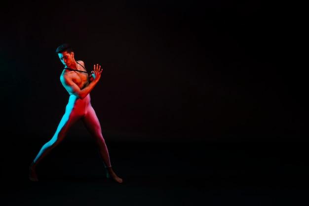Bel homme en justaucorps avec torse nu dansant sous les projecteurs Photo gratuit