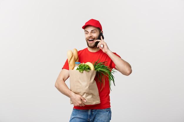 Bel homme de livraison d'épicerie parlant à mobile et tenant le sac de papier d'épicerie. Photo Premium