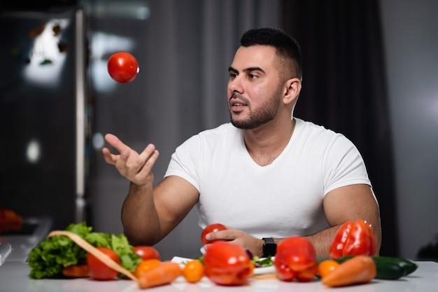 Bel homme à manger des aliments végétariens sains à la maison. le concept d'un mode de vie sain Photo Premium