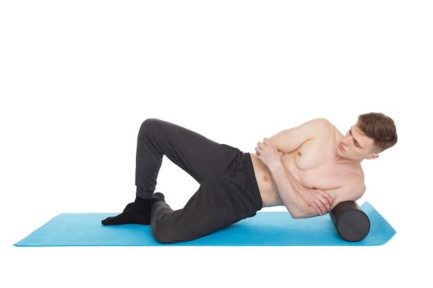 Bel Homme Montre Des Exercices, à L'aide D'un Rouleau En Mousse Pour Un Massage De Libération Myofasciale Sur Un Tapis D'exercice En Studio. Isolé Sur Blanc. Photo Premium