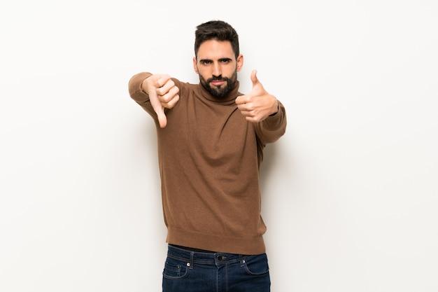 Bel homme sur un mur blanc faisant bon signe. indécis entre oui ou non Photo Premium