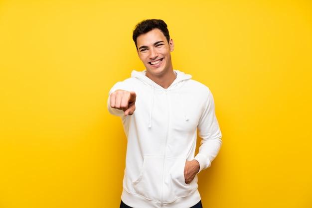 Bel homme sur un mur jaune isolé pointant vers l'avant Photo Premium