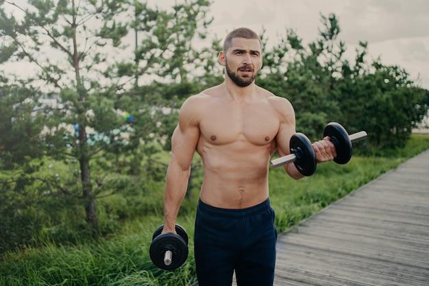 Bel Homme Musclé Soulève Des Haltères à L'extérieur, Fait De La Formation Des Biceps Photo Premium