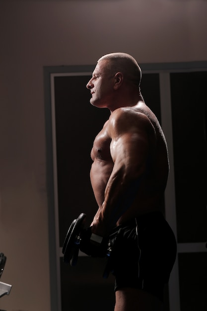Bel homme musclé travaille et pose dans une salle de sport Photo gratuit