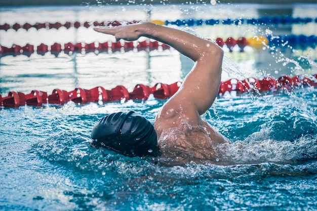 Bel homme nageant dans la piscine Photo Premium