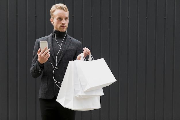 Bel homme en noir avec écouteurs et smartphone Photo gratuit