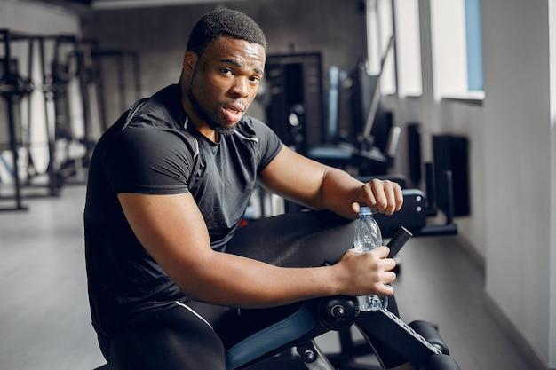 Un Bel Homme Noir Est Engagé Dans Une Salle De Sport Photo gratuit