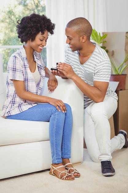Bel homme offrant une bague de fiançailles à sa petite amie dans le salon Photo Premium