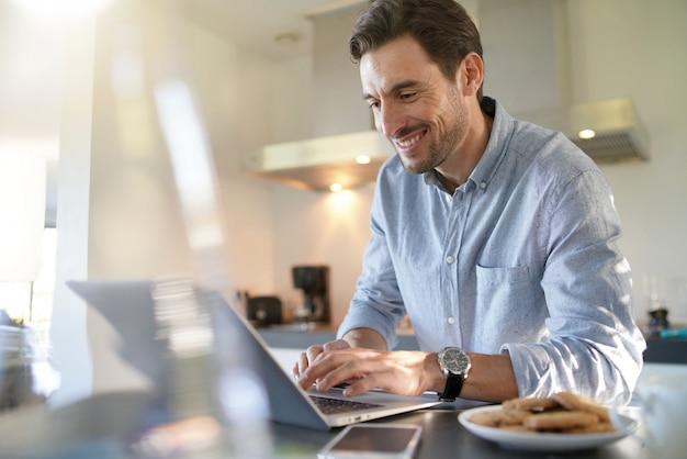 Bel Homme Avec Ordinateur Dans Cuisine Moderne Photo Premium