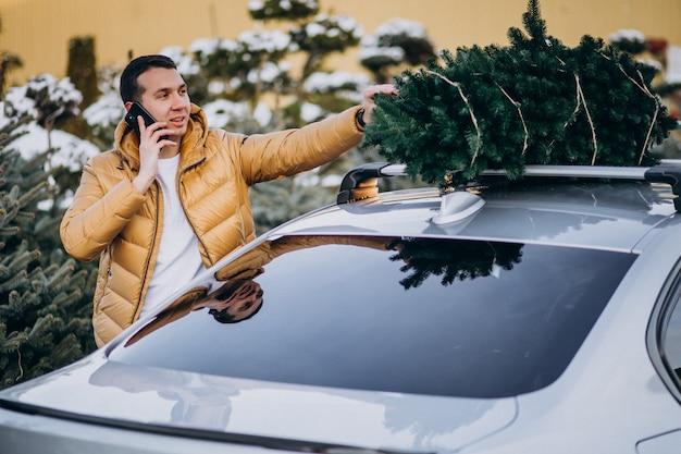 Bel Homme Parlant Au Téléphone Par La Voiture Avec Arbre De Noël Sur Le Dessus Photo gratuit