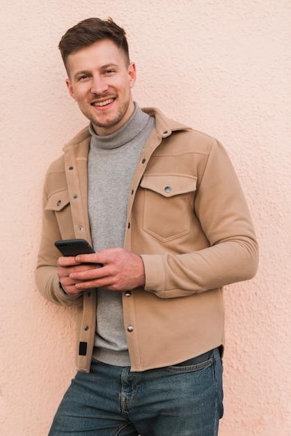 Bel Homme Posant Tout En Tenant Le Smartphone Photo gratuit