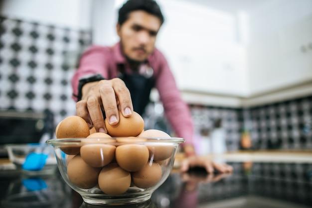 Bel homme prépare des oeufs dans la cuisine. temps de cuisson. Photo gratuit