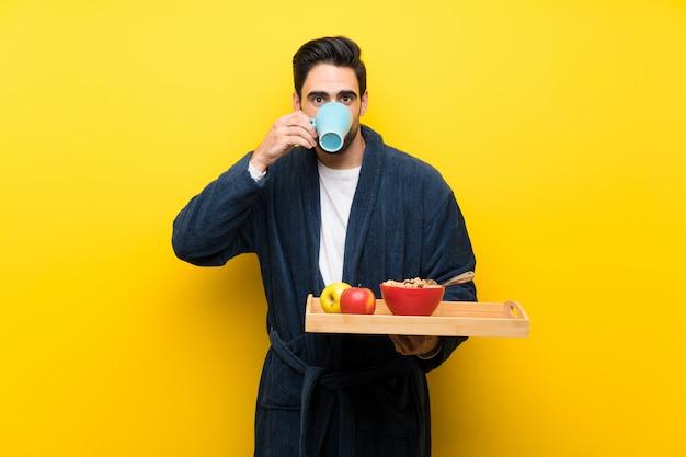 Bel homme en pyjama sur mur jaune isolé Photo Premium